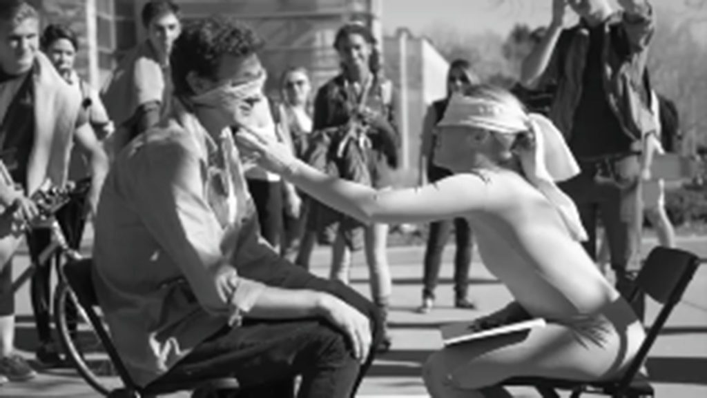 Devan Kallas sits blindfolded on the LSC Plaza, touching the face of a student who sat down across from her.