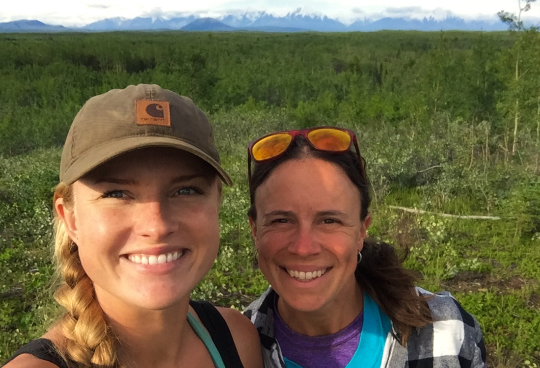 Katherine Sinsky (left) and Kate Yeske (right) surveying at a hilltop site with the Granites of the Alaska Range in the background.