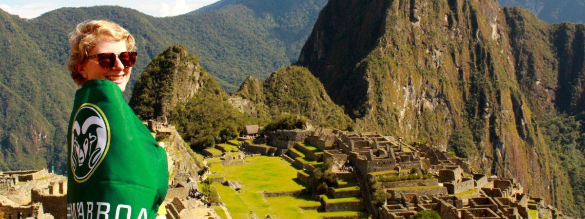Anna Wiig exploring Machu Picchu while wrapped in a CSU flag.
