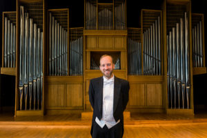 Joel Bacon stands in front of the Casavant Organ