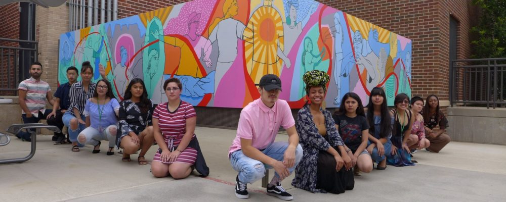 Social Justice Thru the Arts student participants kneeling in front of their collaborative mural