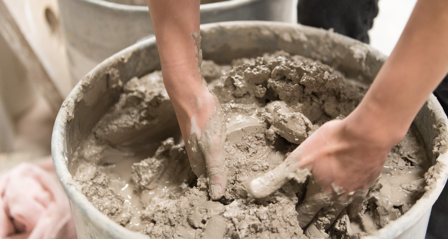 Student mixing clay