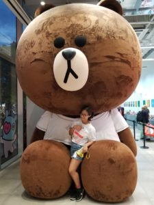 Jayleen Serrano next to a giant stuffed bear in South Korea
