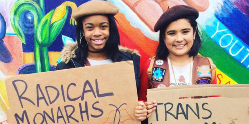 "Two girls at protest holding ""Radical Monarchs"" handmade signs"