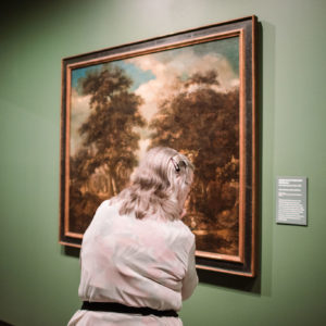 Woman viewing a painting in the Gregory Alllicar Musuem of Art