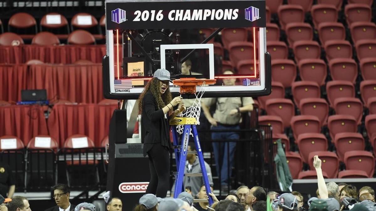 Woman on ladder taking down basketball net