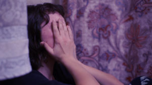 Scene from a student short film: woman on sofa with hands covering her eyes.