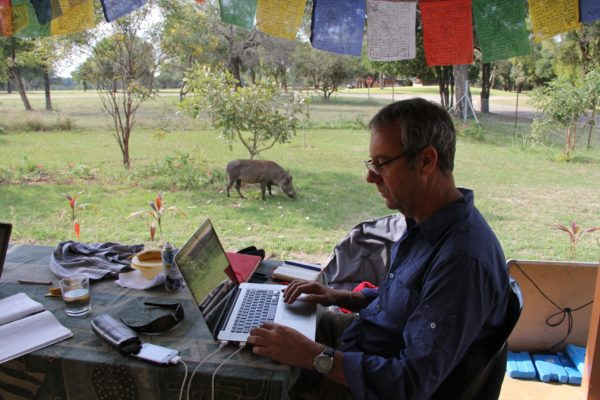David Bunn on a laptop in South Africa with a Warthog in the background
