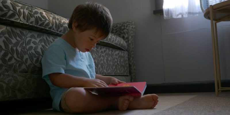Emilio sits reading to himself, screenshot from the Forget Me Not documentary