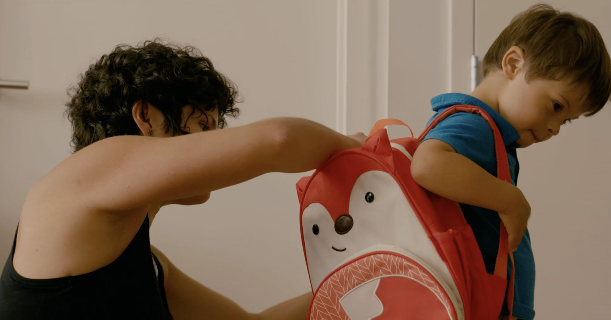 An adult helps a child put on their backpack